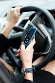 Close-up Of A Businesswoman Sending A Text While Driving