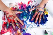 stock photo of messy  - Painted hands smudging colors on messy paper - JPG