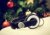 image of christmas song  - Headphones resting on a white leather sofa near the Christmas tree - JPG