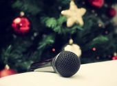 stock photo of christmas song  - Black microphone on white leather sofa near the Christmas tree - JPG