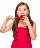 image of love bite  - Portrait of little girl is biting a red heart - JPG