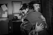 image of office romance  - Detective consoling and hugging a young woman in his office film noir scene - JPG