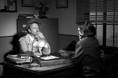 stock photo of 1950s style  - Handsome detective at office desk interviewing a young woman 1950s film noir style - JPG