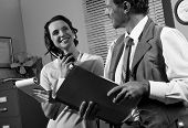 picture of 1950s style  - Young secretary on the phone and director working together 1950s vintage style office.