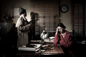 stock photo of nervous breakdown  - Confident detective standing in his office interviewing a young sad woman - JPG