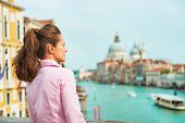 picture of piccolo  - Young woman looking into distance while standing on bridge with grand canal view in venice italy - JPG