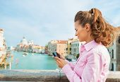 foto of piccolo  - Young woman standing on bridge with grand canal view in venice italy and checking photos in camera - JPG