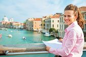 stock photo of piccolo  - Portrait of happy young woman with map standing on bridge with grand canal view in venice italy - JPG