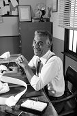 image of 1950s style  - Smiling professional accountant working at desk 1950s style office - JPG
