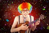 stock photo of wig  - Geeky hipster in afro rainbow wig playing guitar against colourful fireworks exploding on black background - JPG