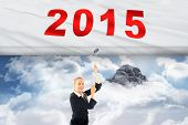 stock photo of mountain chain  - Businesswoman pulling a chain against mountain peak through the clouds - JPG