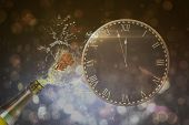 picture of count down  - Clock counting down to midnight against champagne popping - JPG