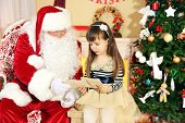 picture of letters to santa claus  - Little cute girl giving letter with wishes to Santa Claus near Christmas tree at home - JPG