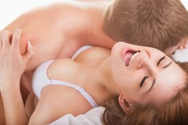 stock photo of intimate  - Young beautiful amorous couple making love in bed on white background - JPG
