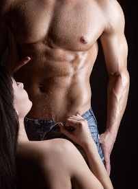 stock photo of enamored  - Young woman undressing muscular man on dark background - JPG