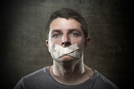 foto of freedom speech  - attractive young man with mouth sealed on duct tape to prevent him from speaking keeping him mute and censored in freedom of speech and expression concept - JPG