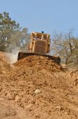 stock photo of bulldozer  - Large bulldozer moving rock and soil for fill for a new commercial development road construction project - JPG