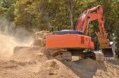 stock photo of track-hoe  - Large bulldozer and track hoe excavator moving rock and soil for fill for a new commercial development road construction project - JPG