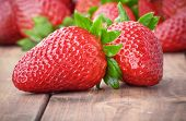 image of foreground  - two strawberries closeup on the foreground and on blurred background heap of strawberries - JPG