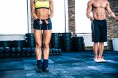 pic of gym workout  - Man and woman workout with jumping rope at crossfit gym - JPG
