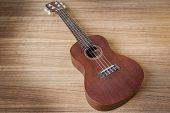 stock photo of ukulele  - A Vintage ukulele on wooden background  - JPG