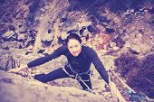 stock photo of climbing wall  - Vintage style filtered picture of a young woman climbing wall - JPG