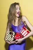 picture of jumpsuits  - Surprised smiling girl in violet jumpsuit holding colorful boxes of presents standing on yellow background vertical photo - JPG