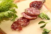 image of kangaroo  - sausage slices from a kangaroo on wooden to a board - JPG