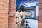 picture of automatic teller machine  - Woman with backpack withdrawing money from credit card at ATM - JPG