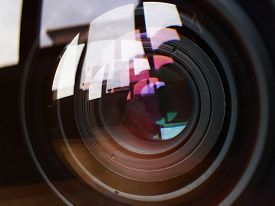 stock photo of reflections  - Macro shot of front element of a camera lens with beautiful color lights reflections - JPG