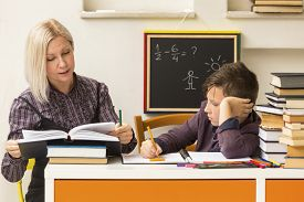 stock photo of schoolboys  - Schoolboy is learning with the teacher - JPG