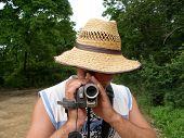 stock photo of leghorn  - the man with the videocamera traveler hat - JPG