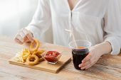 Постер, плакат: fast food people and unhealthy eating concept close up of woman eating deep fried squid rings fr