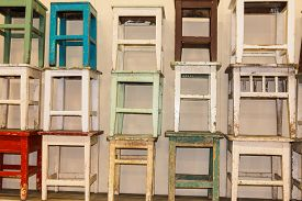 stock photo of stool  - A bunch of worn and colorful stacked stools - JPG