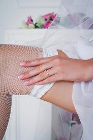 picture of garter-belt  - The bride holds the white lace garter in the studio - JPG