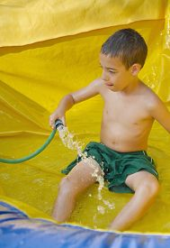 picture of inflatable slide  - 8 year old boy enjoying the summer while playing on a wet inflatable slide - JPG
