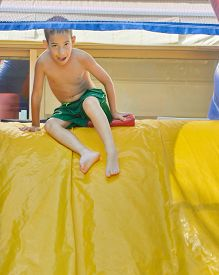 image of inflatable slide  - 8 year old boy enjoying the summer while playing on a wet inflatable slide - JPG