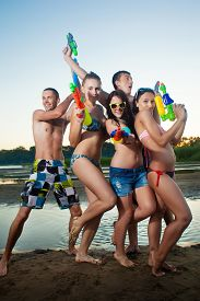 foto of pistols  - Group of young joyful young people playing and posing with water pistols on the beach  - JPG