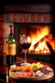 foto of cozy hearth  - Wine bottle and partially filled glass with assorted food on a wooden serving plate - JPG