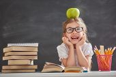 Back to school and happy time! Cute industrious child is sitting at a desk indoors. Kid is learning  poster