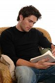pic of young men  - A handsome young man in a chair reading a book - JPG