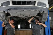 foto of car repair shop  - Auto mechanics working under the car  - JPG