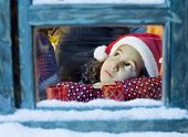 pic of santa claus hat  - Little girl with a Santa hat  looking outside - JPG