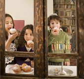 children in front of a Hanukkia eating traditional jelly doughnut in Hanukka