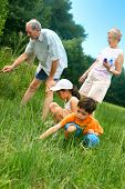 picture of priceless  - Young children outdoors looking for insects and wildlife with the grandparents - JPG