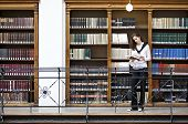 stock photo of girl reading book  - Young attractive woman standing in front of bookshelf in old university library reading a book - JPG