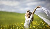 stock photo of flutter  - Young happy woman standing in yellow rapeseed field holding a white piece of cloth in the wind expressing freedom - JPG