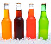 Closeup of four assorted soda bottles standing in ice with condensation. Horizontal format over a wh