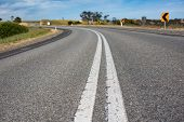 Close Up Of Asphalt Road In Australian Countryside. Rural Infrastructure Landscape With Winding Road poster