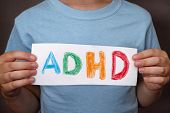 Young Boy Holds Adhd Text Written On Sheet Of Paper. Adhd Is Attention Deficit Hyperactivity Disorde poster
